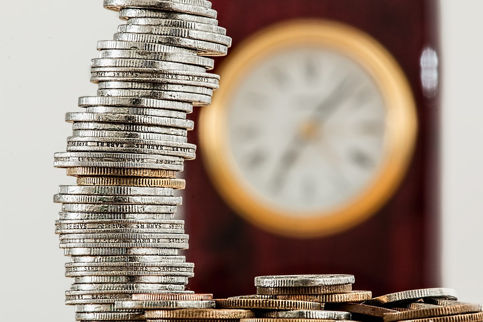 saving money: huge pile of coins on table with clock in background on wall.