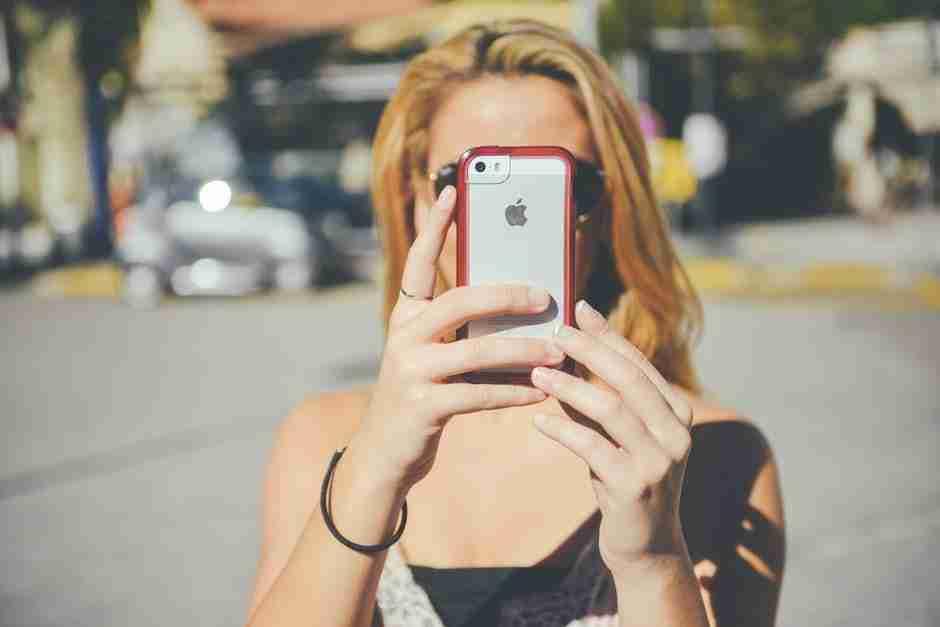 Best Ever Selfie: Blonde young woman taking selfie in street