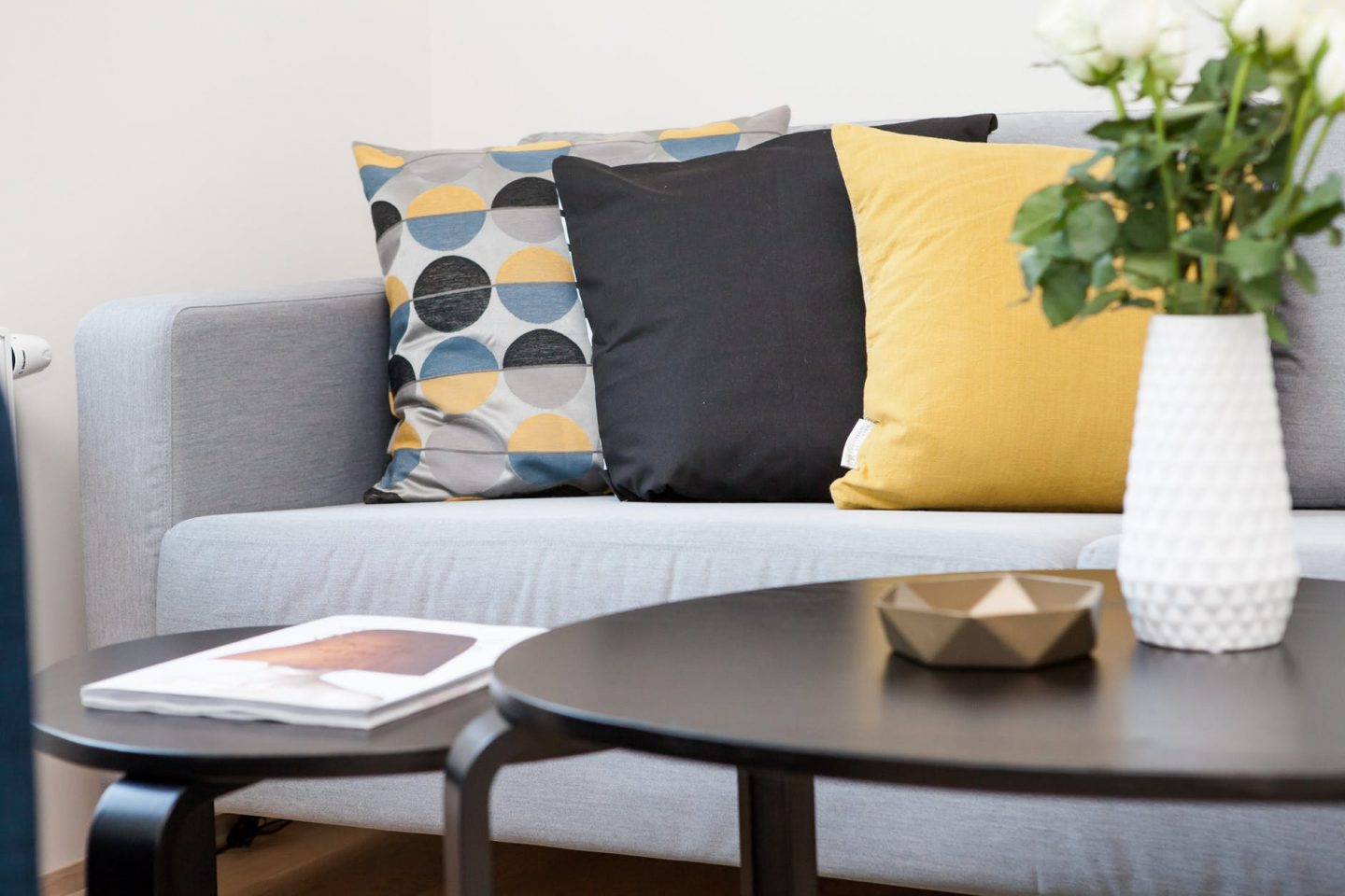versatile decor: Dark brown coffee table in front of grey sofa with multi-coloured cushions