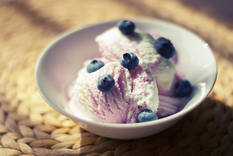 White bowl of strawberry ice-cream with blueberries on top.