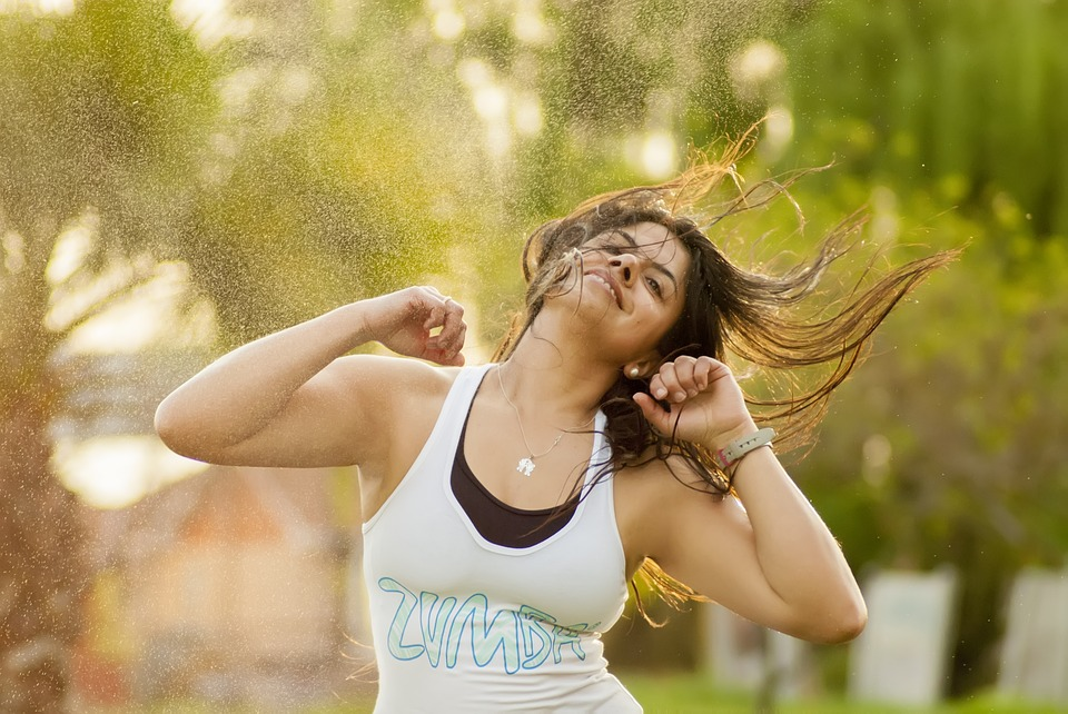 Young woman at Zumba dancing class in green park: fun with friends