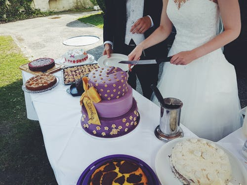 your big day: couple cutting wedding cake in garden.