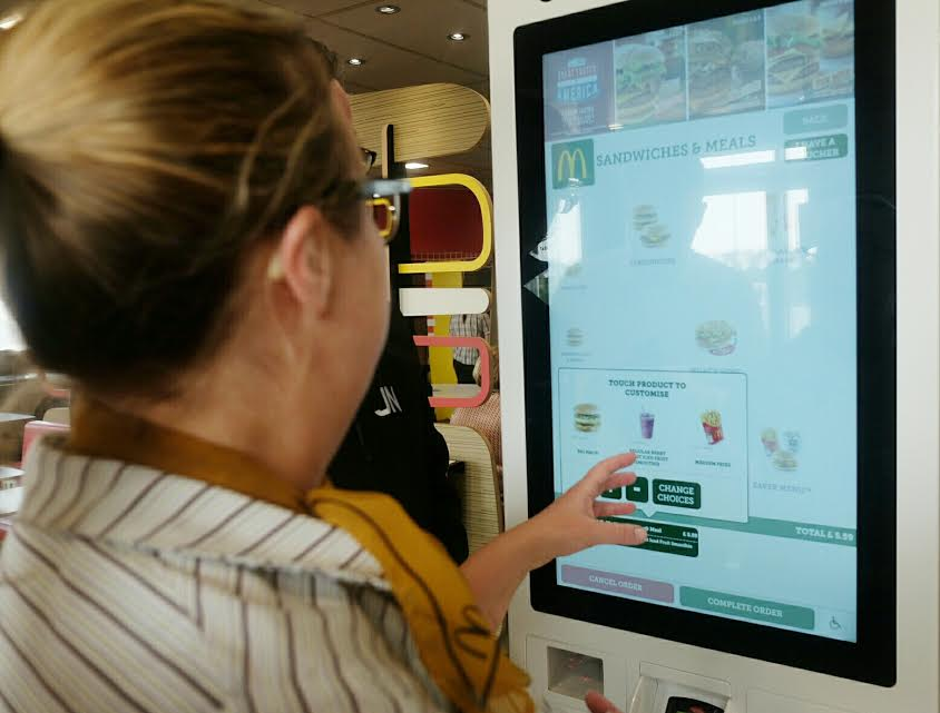 McDonalds Restaurant employee demonstrating touchscreen menu