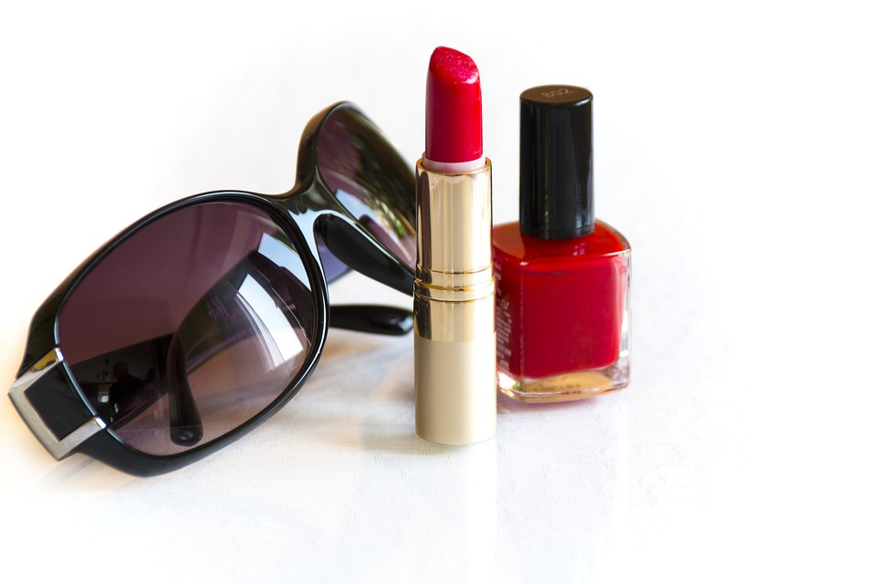 Red open lipstick beside sunglasses and red nail polish on table.