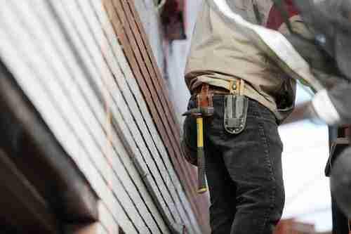 Fixes: man wearing black denim pants carrying hammer on holster.