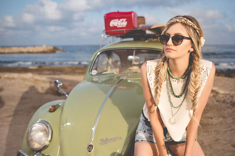 festival look: young blond girl in front of green Volkswagon Beetle by a beach.