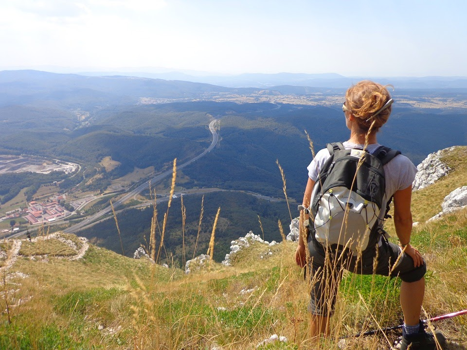 hiking holidays: young man lookig oout over a valley in sunshine.