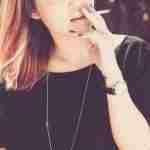 giving up smoking: woman in black top smoking.