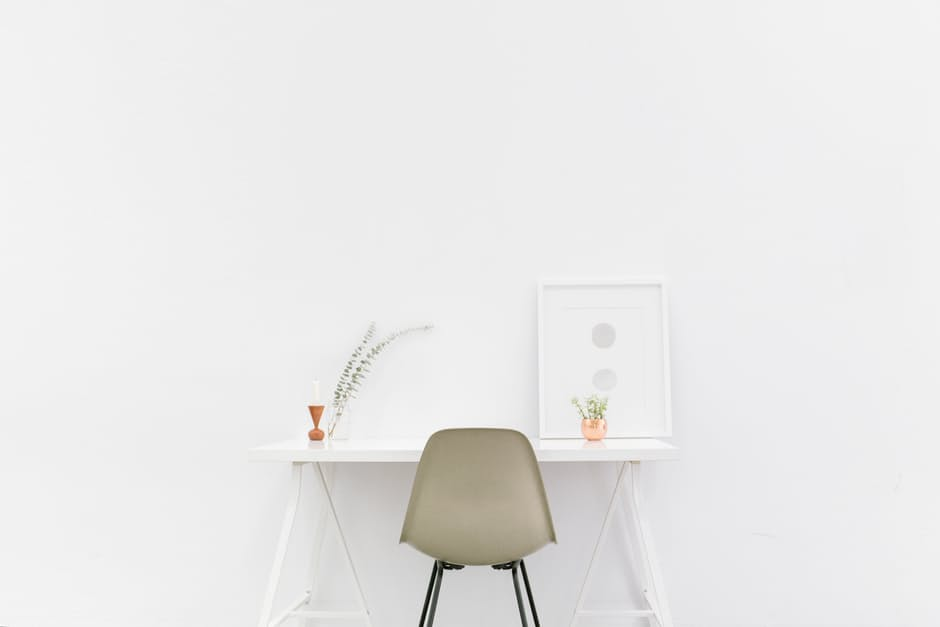 beige chair up against white small table in bare room. Minimalist makeovers.