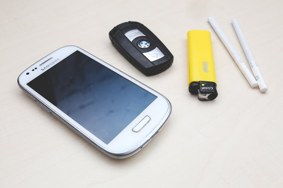 modern bad habits: smartphone, car key, cigarettes and yellow lighter on a white table.