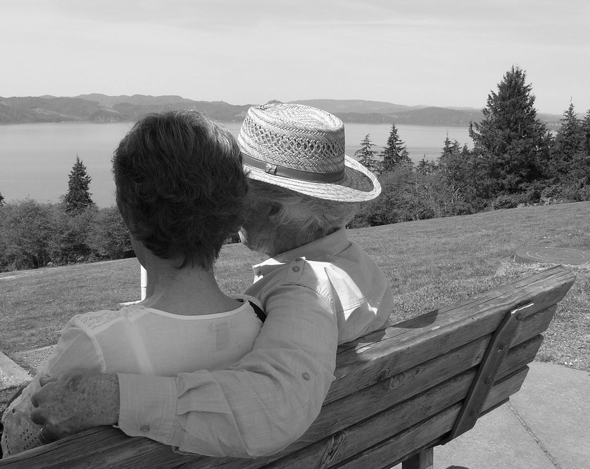 couple sitting on a bench looking out at a lake: dating tips for over 50's