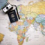 US passport and camera on a world map: international travel for beginners