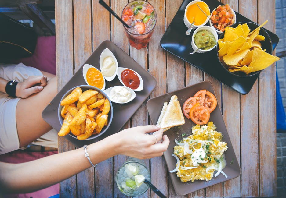 weight loss: person eating unhealthy snacks on a wooden restaurant table.