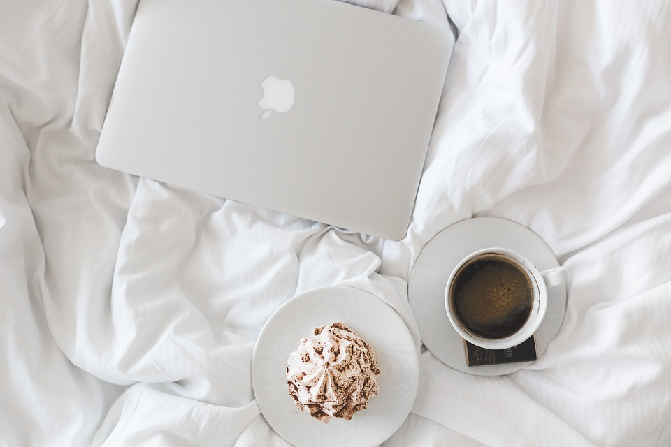 what to do after a fall: coffee, cupcake and laptop on a white duvet