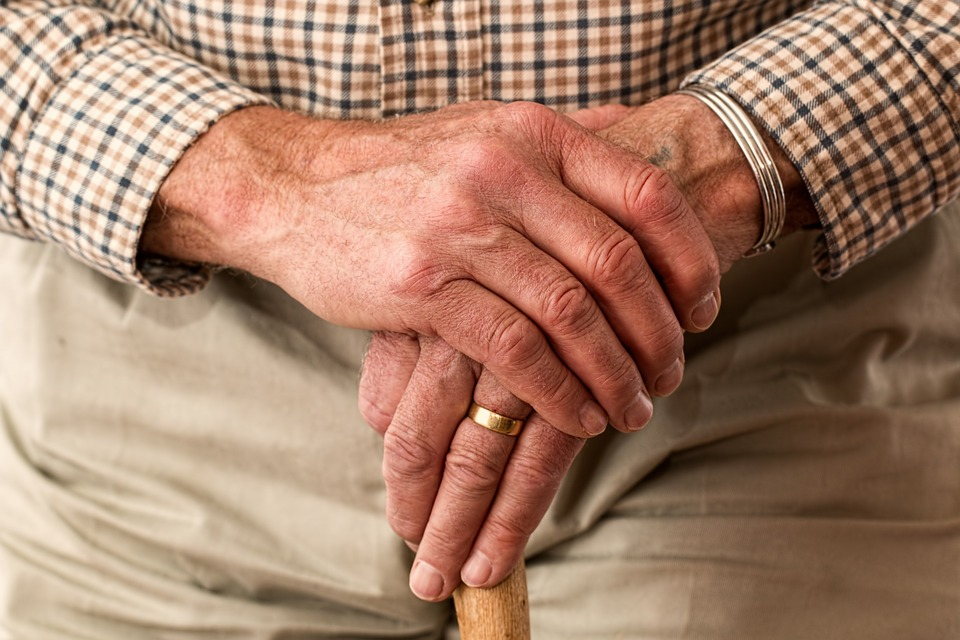 An elderly man holding one hand in the other, wearing a brown, white and black chequered shirt and khakis.