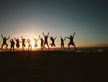 choose happiness: group of people jumping for joy in evening sun