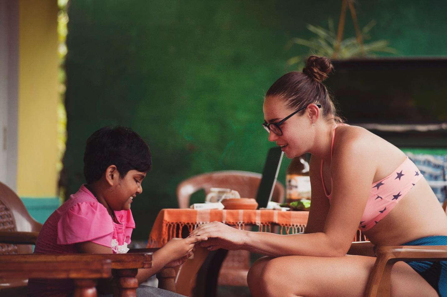 make the most of volunteering abroad: young woman talking to child in a classroom
