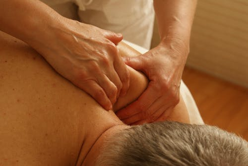 older grey-haired man getting a shoulder massage.