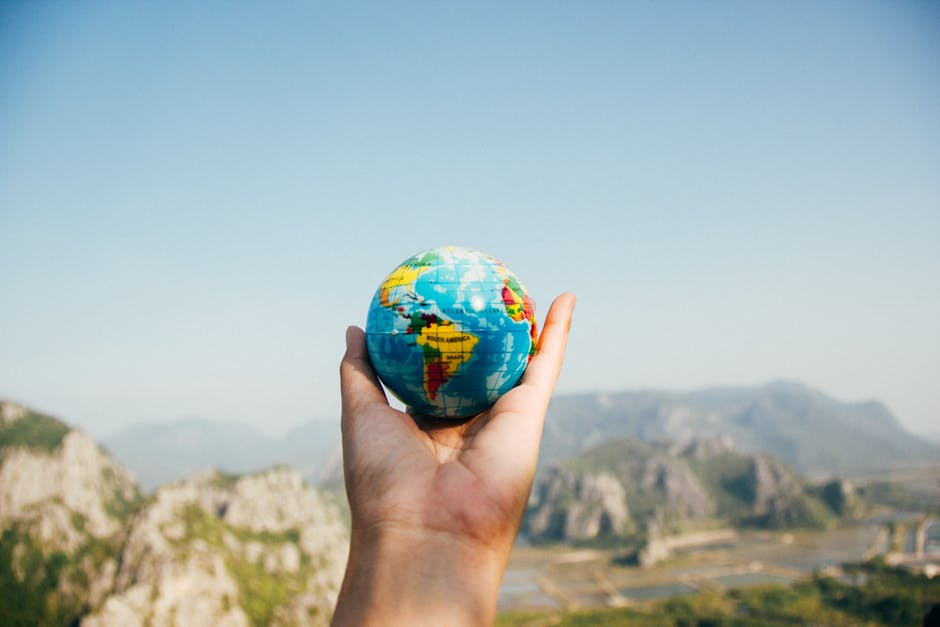 Person holding up a globe: expat life