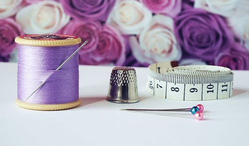Hobby: spool of purple thread near needle, thimble and measuring tape.