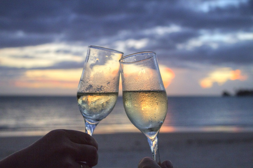 planning the perfect honeymoon: 2 champagne glasses full of champagne.