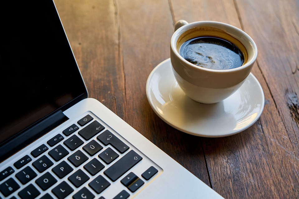 Local dating sites: Laptop and cup of coffee on wooden table