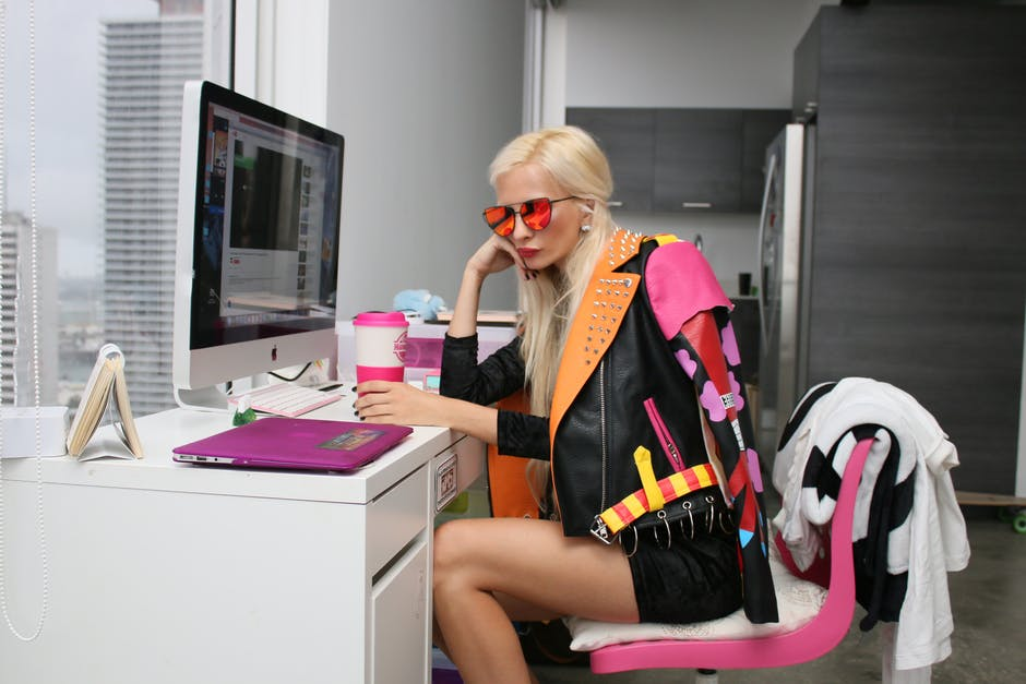 Blond haired tall slim young lady in black and pink clothing dressing against the norm.