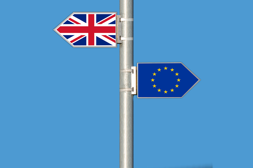 Brexit: silver flag pole with a GB and a EU flag each pointing in opposite direction.