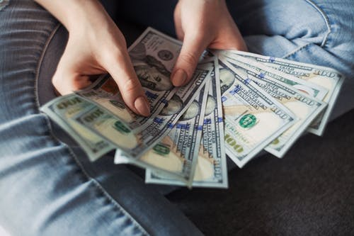 man holding dollar bills: make your income go further.