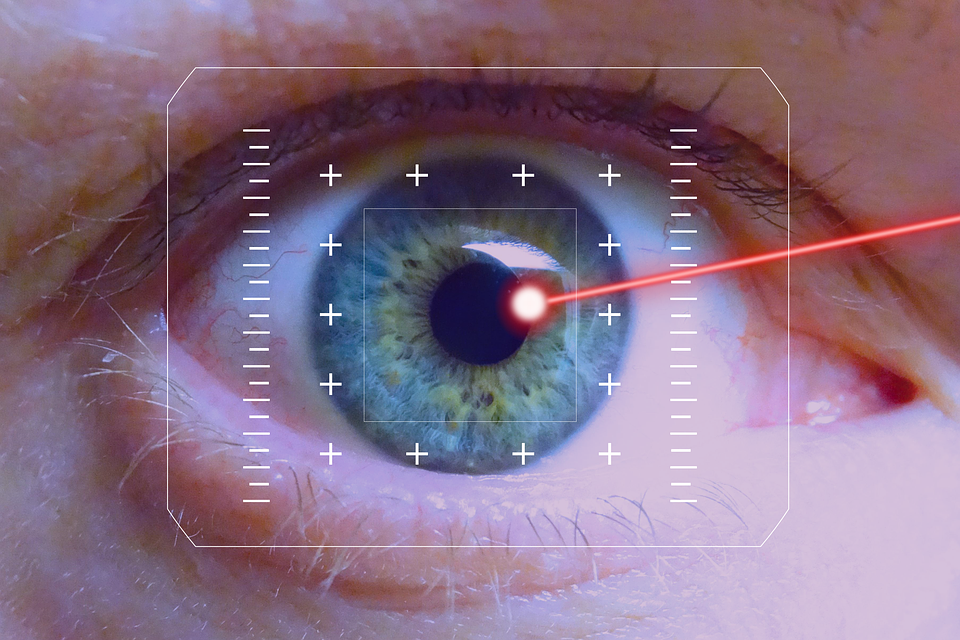 close up of an eye with a laser pointing at the iris : LASIK eye surgeon