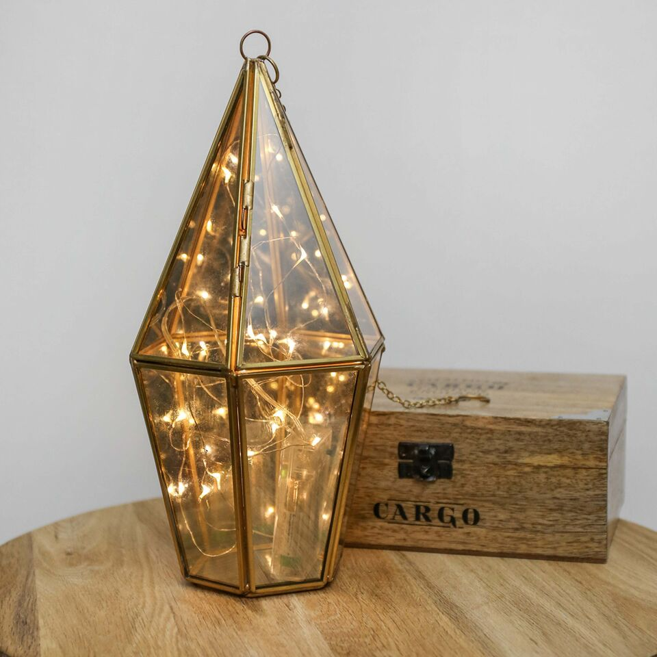 lighting design: small table top terrarium with a string of fairy lights inside it on a wood table