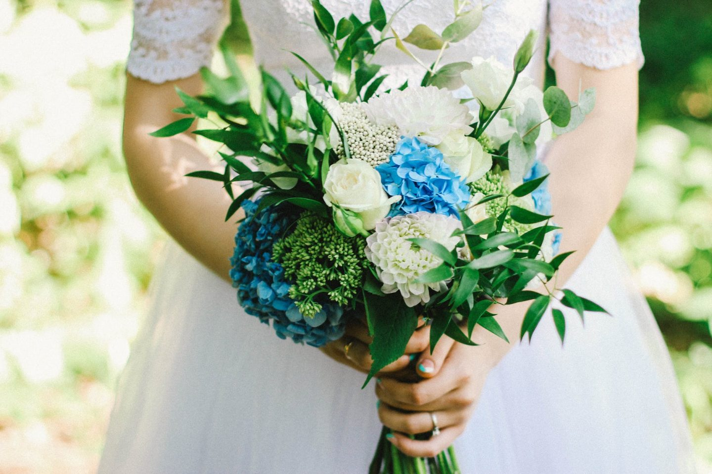 blue and white bouquet being held by a bride in a white dress: springtime wedding.
