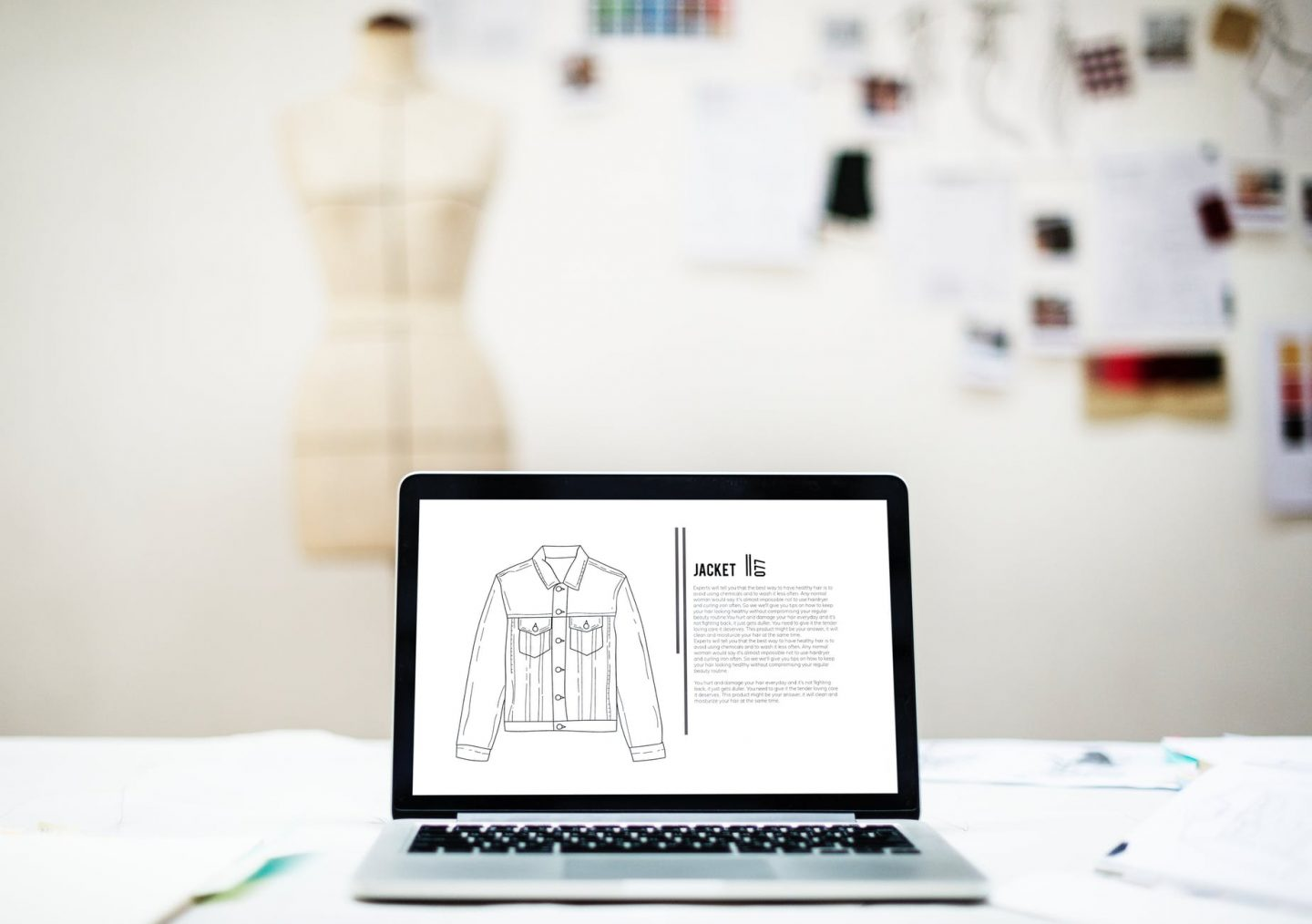 body contour fashion: open laptop with sketch of a jacket with blurred image of mannequin in the background
