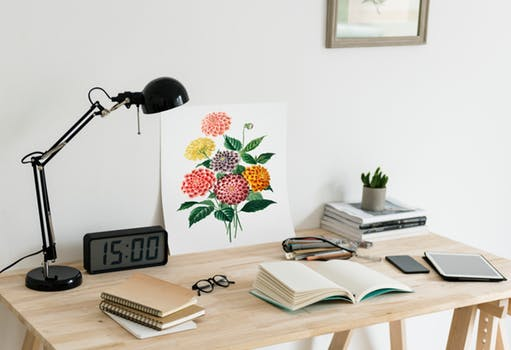 lighting design: wooden desk with a black table lamp, books, and an alarm clock showing 3pm