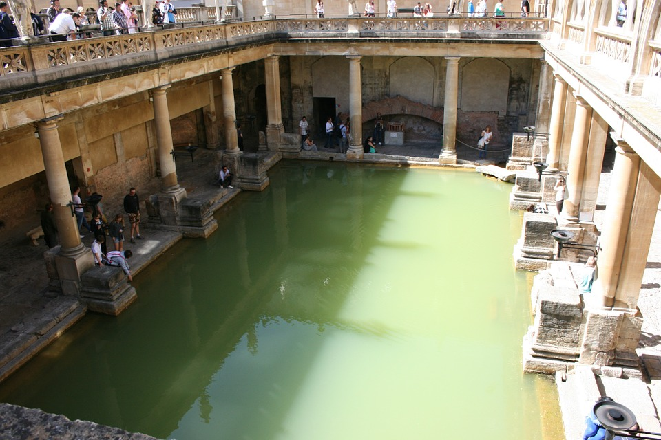 visiting the UK: view from above down to roman baths, sunny day,with tourists looking down