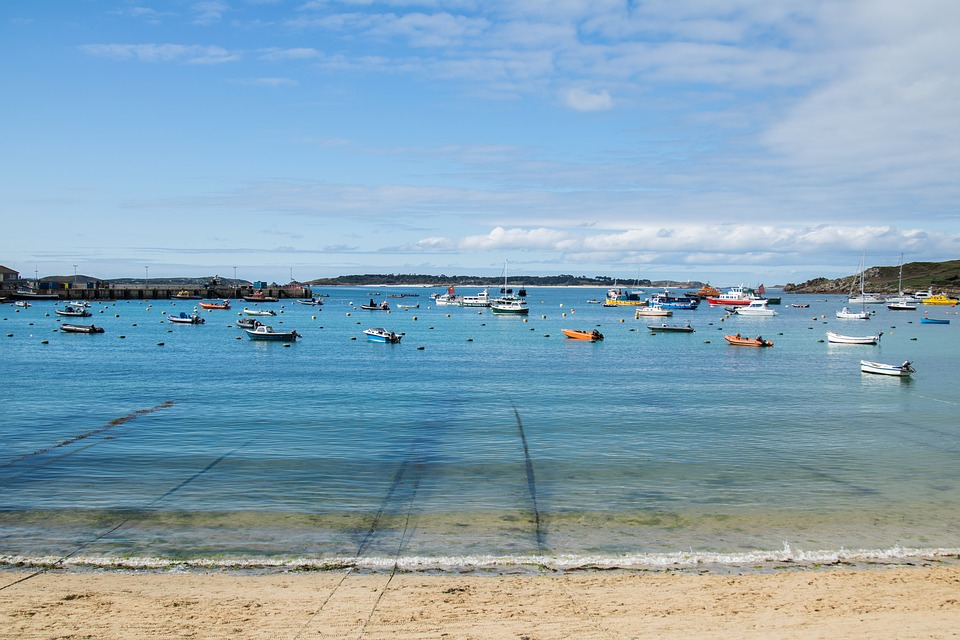 visiting the UK: view from beach of sea with lots of small boats and clear water