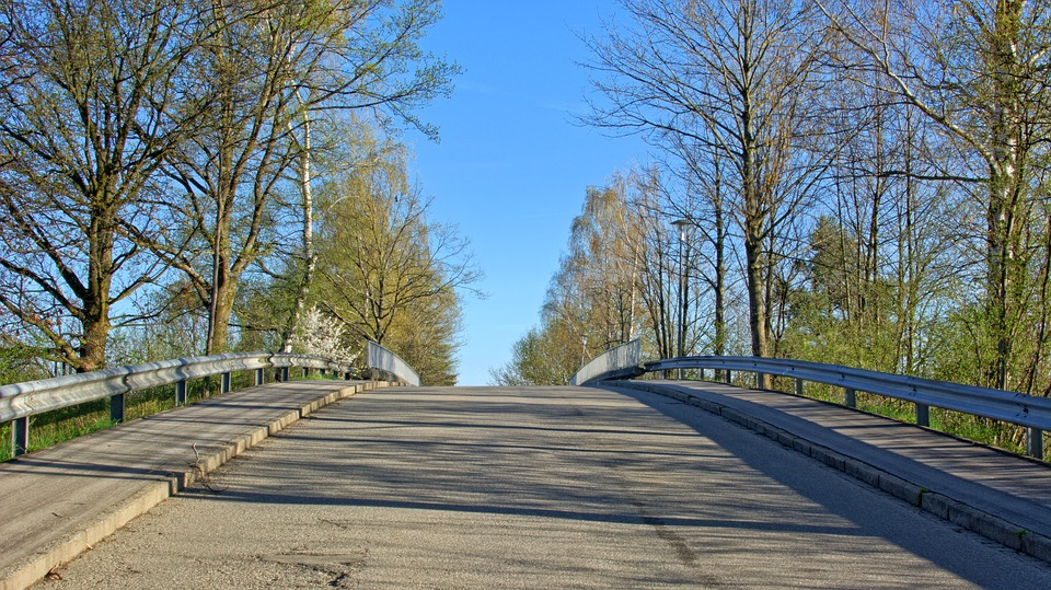 Photo of open road on a sunny with crash barriers on either side of road.