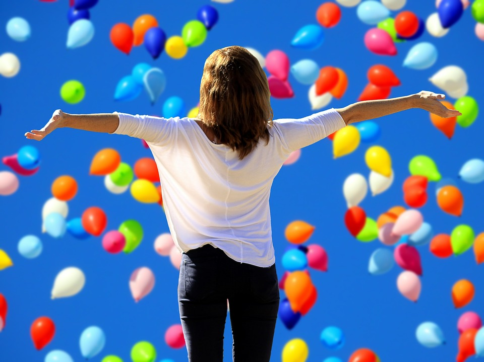 Woman with outstretched arms looking at the release of many multi-coloured balloons into the clear blue sky.