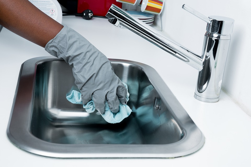 clean: man cleaning sink basin.