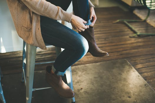 Fast fashion: Woman sitting on wooden bar stool folding up the bottom of the leg of her jeans.