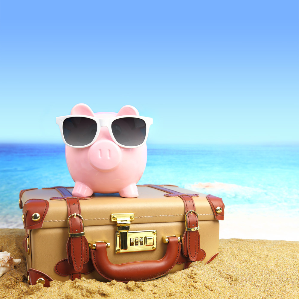 Debt: Piggy bank with sunglasses on top of suitcase on a beach
