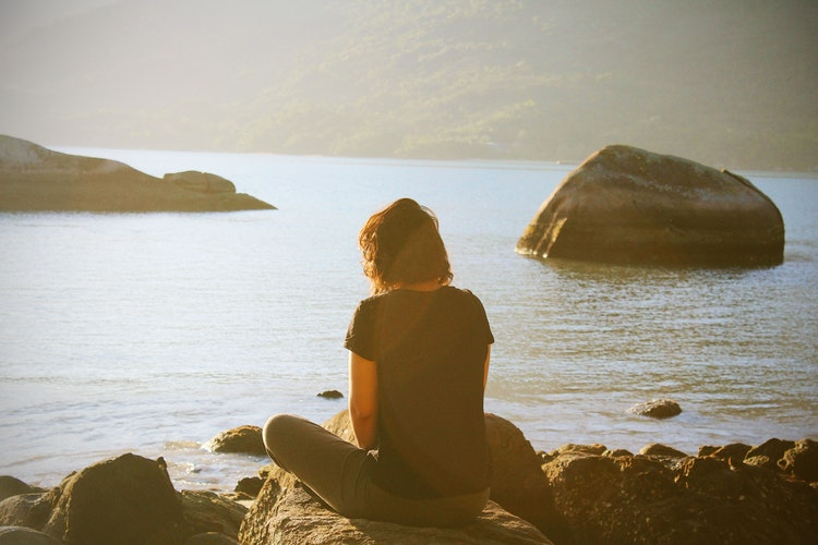 grief: young woman sitting on rock looking at the sea on a sunny day.