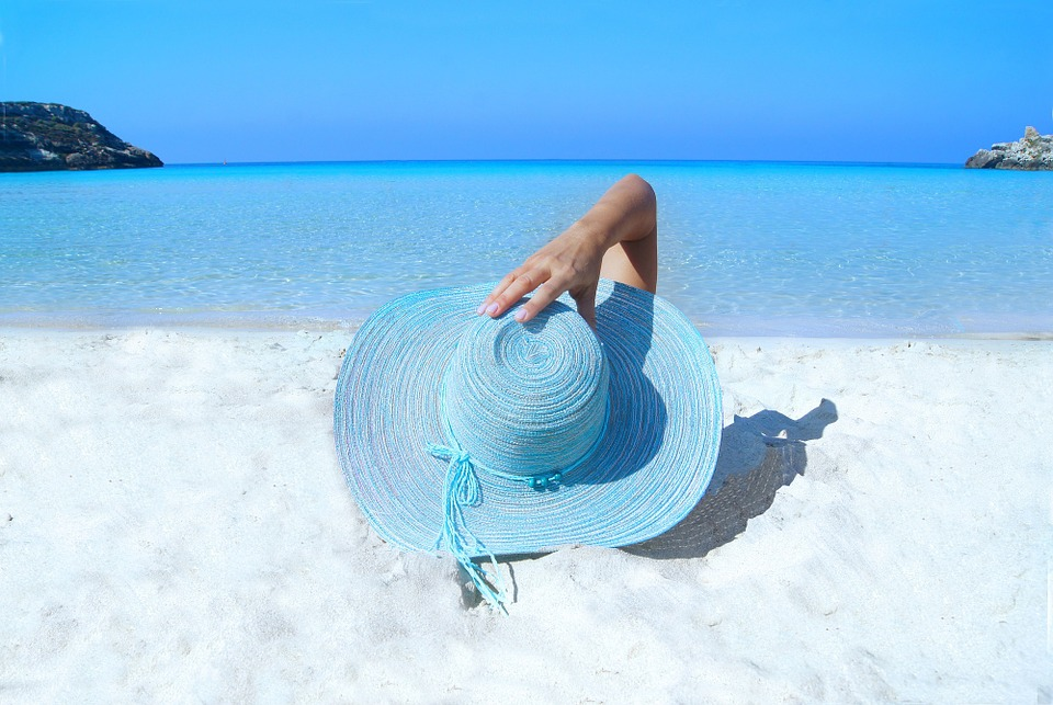 Woman holding on light blue sun hat lying on white sandy beach by light blue ocean.