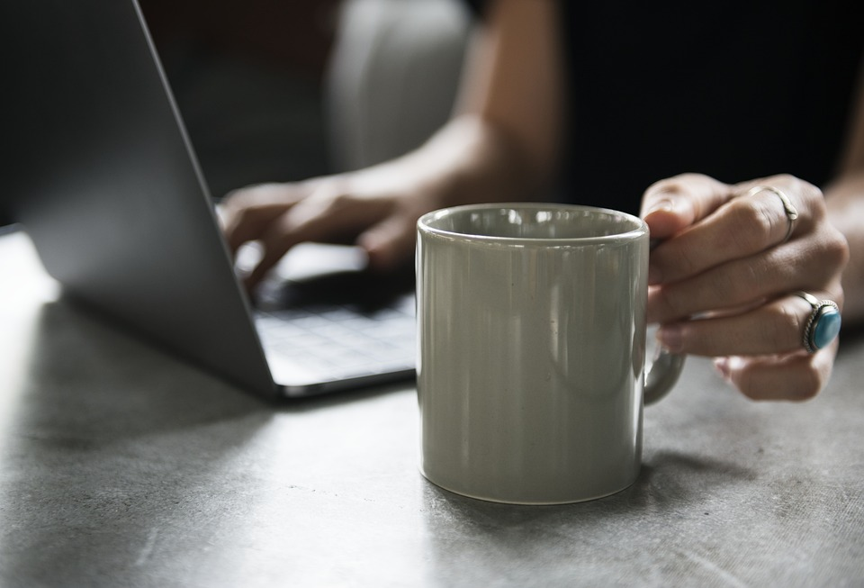 save money on your holidays: woman on laptop and holding a mug.