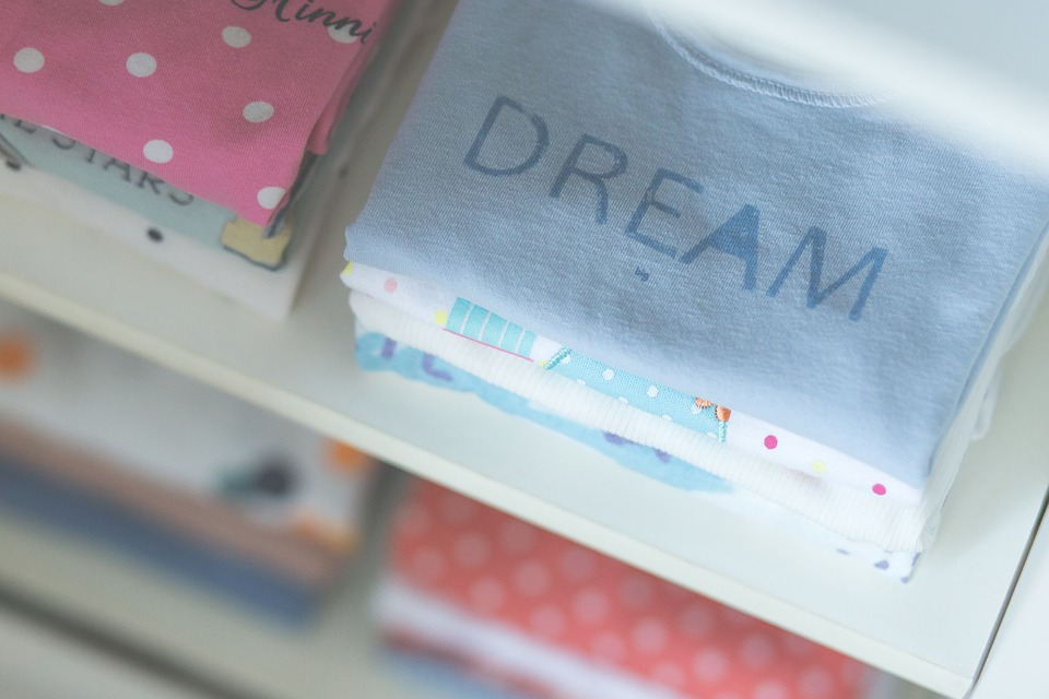 children's fashion: shop shelf with t-shirts folded.