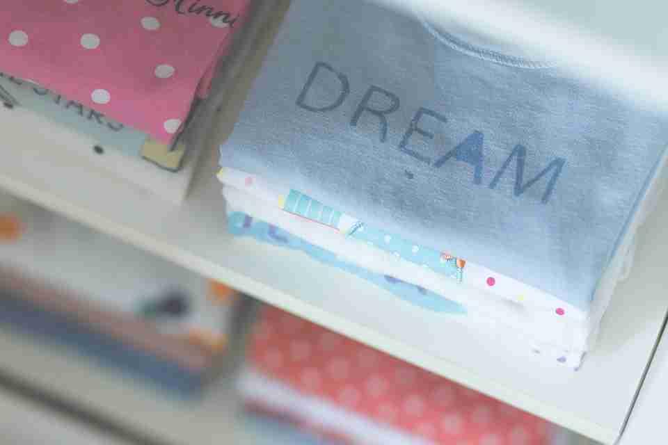 children's fashion: shop shelf with t-shirts folded.