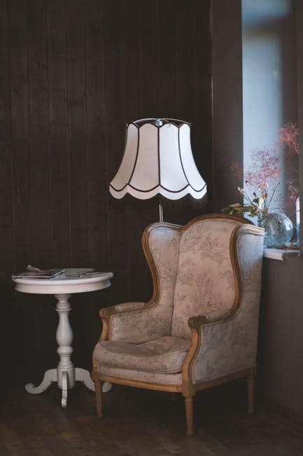 interior design hacks: large sofa chair and lamp and small table in corner of room.