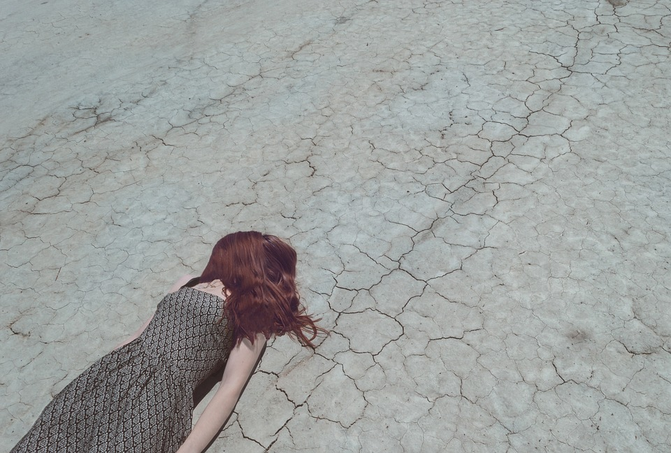 celebrity hairstyle trends: woman lying on ground with her red hair over her face