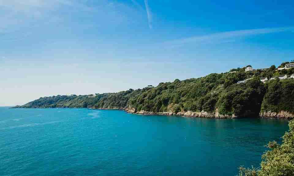 Visit Guernsey: coastline with blue sea.