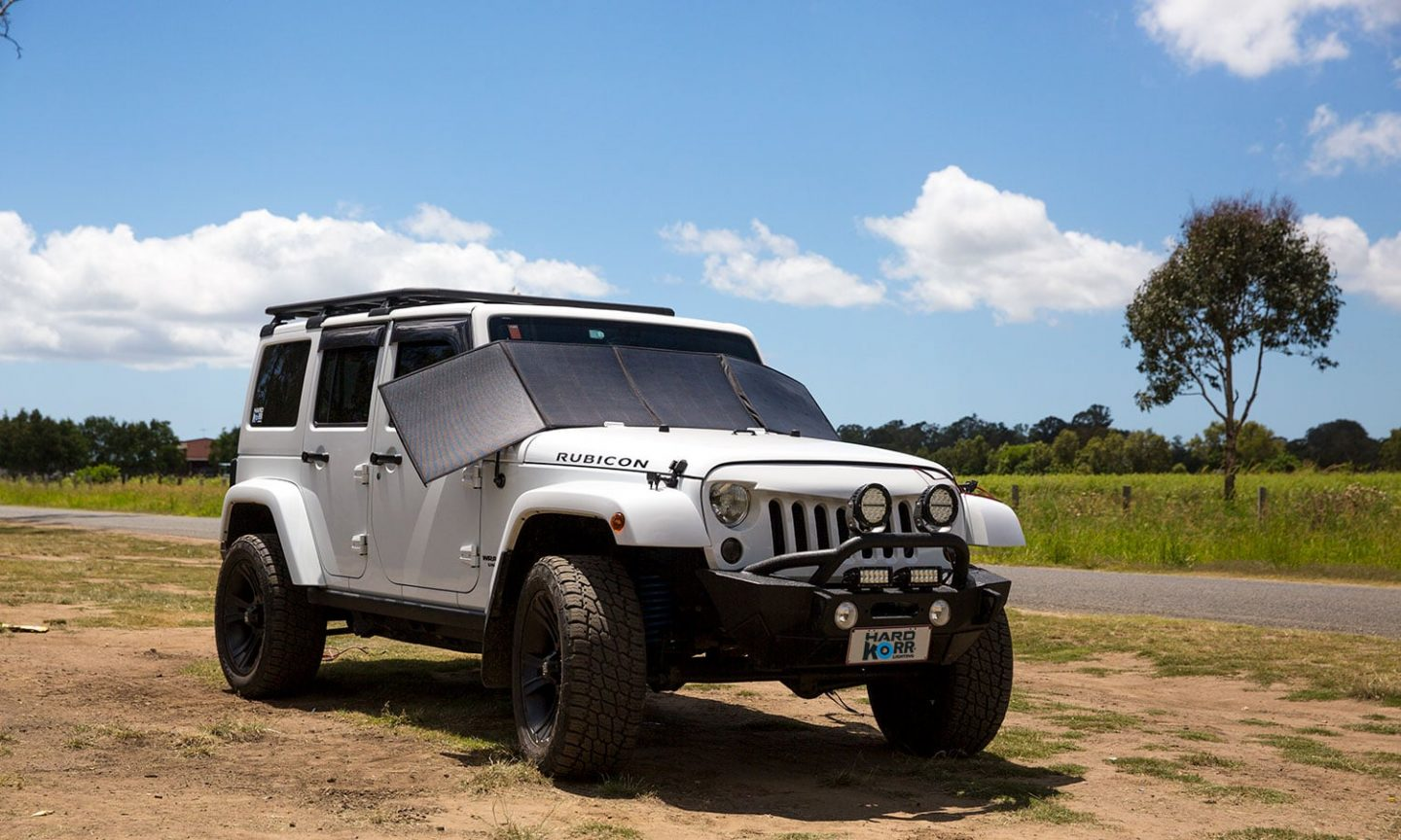 camping trip with your family: white Rubicon jeep on side of road.